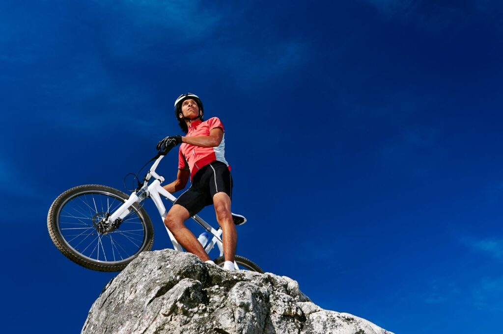Man on cliff with a bicycle